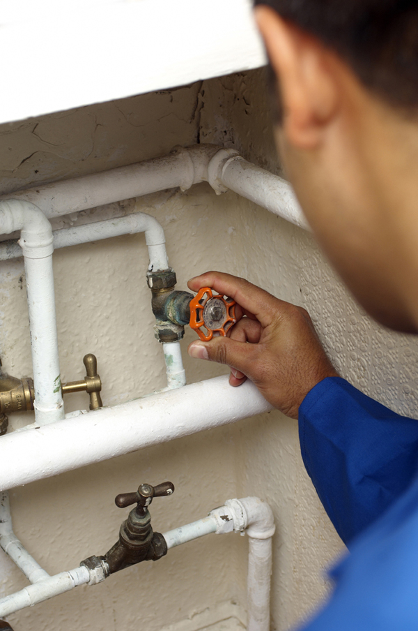 Berkeley Plumbing associate adjusts gate valve